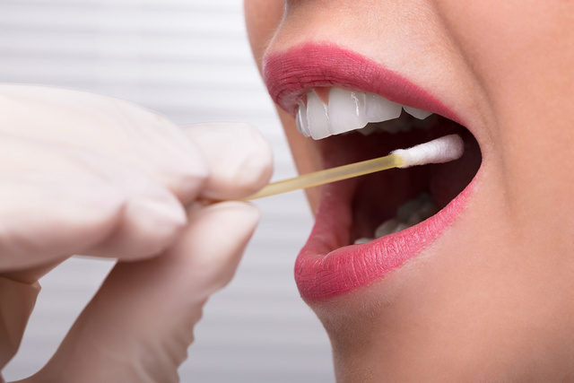 Dentist's Hand Taking Saliva Test From Woman's Mouth - monte mare