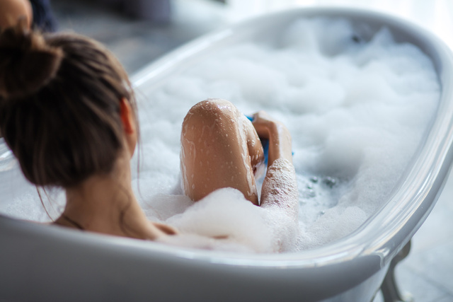 female massaging her legs with sponge in the tub - Unternehmensgruppe