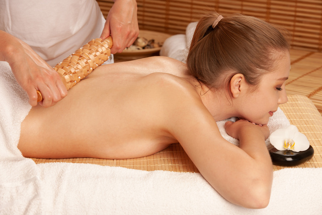 Beautiful young woman having a maderotherapy massage  treatment in spa salon - wellness - Unternehmensgruppe
