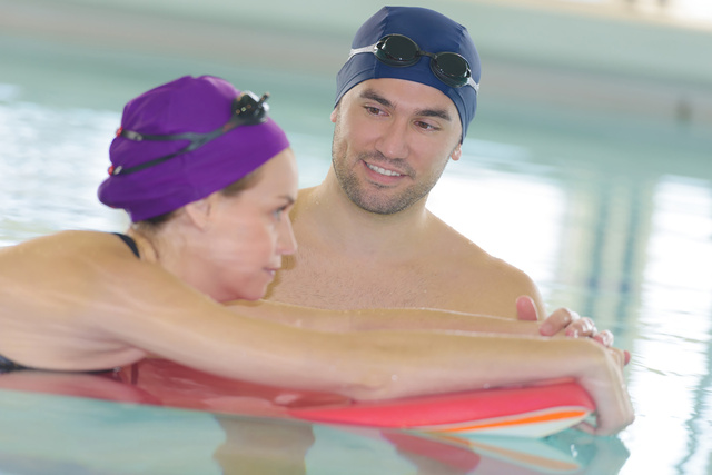 man helping woman in swimming pool with float - Unternehmensgruppe